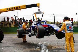 Des commissaires enlevant la voiture endommagée d'Alexander Albon, Toro Rosso STR14, du circuit après son crash en fin des EL3