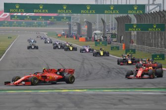 Charles Leclerc, Ferrari SF90, voor Sebastian Vettel, Ferrari SF90, Max Verstappen, Red Bull Racing RB15, Pierre Gasly, Red Bull Racing RB15, Daniel Ricciardo, Renault F1 Team R.S.19, Sergio Perez, Racing Point RP19, and the remainder of the field on the opening lap