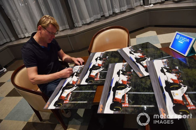 Mika Hakkinen signs photos from his 1993 Australian GP practice flight