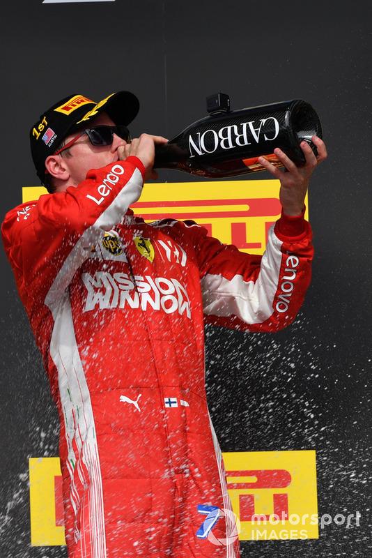 Race winner Kimi Raikkonen, Ferrari celebrates on the podium with the champagne