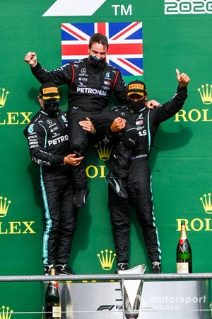 Valtteri Bottas, Mercedes-AMG F1, 2nd position, and Lewis Hamilton, Mercedes-AMG F1, 1st position, lift their team mate in the air