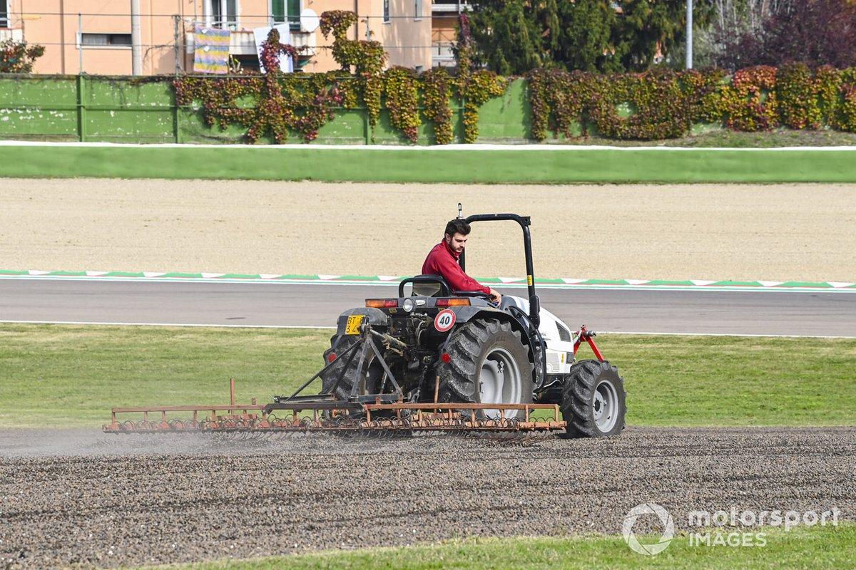 Una trampa de grava se rastrilla y se riega con un tractor.