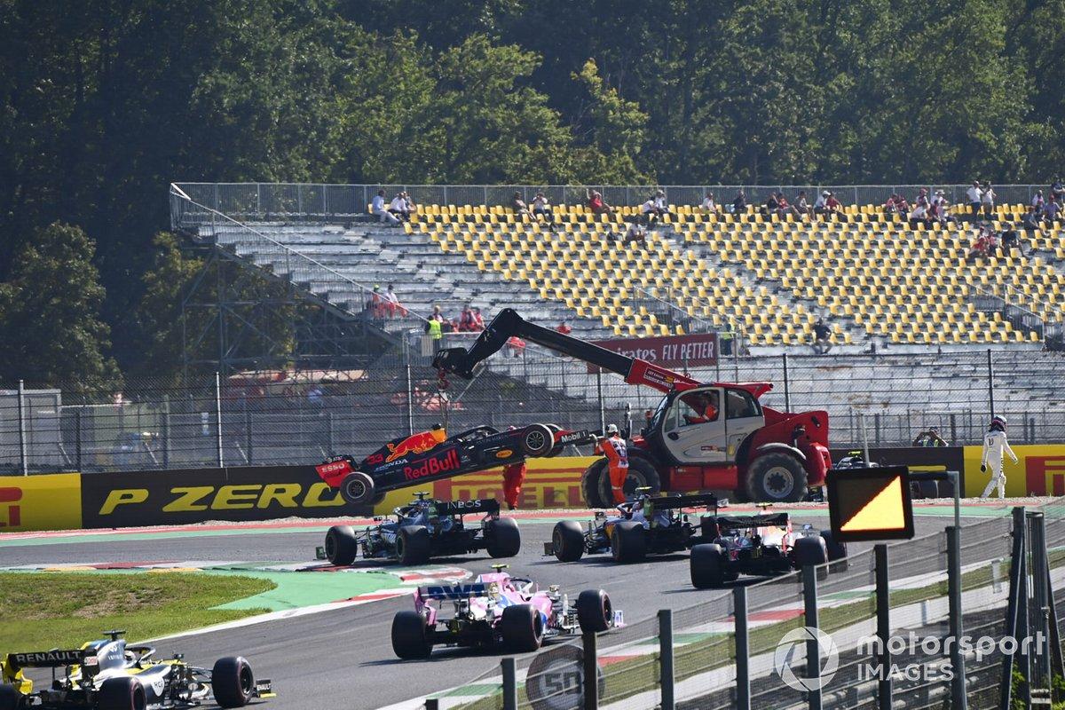Oficiales de pista remueven el monoplaza de Max Verstappen, Red Bull Racing RB16, mientras pasa Lewis Hamilton, Mercedes F1 W11