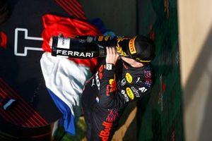 Max Verstappen, Red Bull Racing, 1a posizione, festeggia sul podio indossando la bandiera olandese