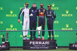 George Russell, Williams, 2nd position, the Red Bull trophy delegate, Max Verstappen, Red Bull Racing, 1st position, and Lewis Hamilton, Mercedes, 3rd position, on the podium