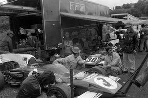 Mechanics work on Jacky Ickx's Ferrari 312B2 in the paddock