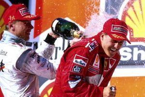 Podio: ganador de la carrera Mika Hakkinen, Mclaren rocía el segundo puesto Michael Schumacher, Ferrari con champán