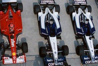Michael Schumacher parcheggia la sua Ferrari F2001 vicino alla Williams FW24 di Ralf Schumacher e Juan Pablo Montoya nel parc fèrmè
