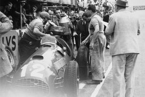 Alberto Ascari looks on Jose Froilan Gonzalez, Ferrari 375 makes a pit stop after Ferrari's first GP victory.
