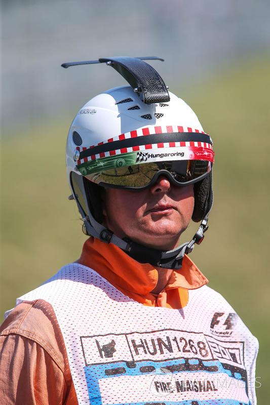 Oficial de pista con un casco
