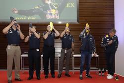 Гонщик Red Bull Racing Даниэль Риккардо и приглашенные гости пьют шампанское из ботинок в штаб-квартире ExxonMobil