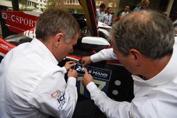 Des membres de l'équipe IDEC Sport Racing placent un autocollant Le Mans