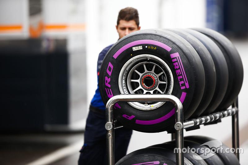 Un membro di un team attraversa il paddock con degli pneumatici Pirelli