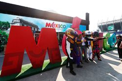 Fans pose with helmeted mascots in front of a large Mexico sign