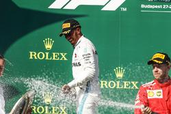 Lewis Hamilton, Mercedes AMG F1, 1st position, and Sebastian Vettel, Ferrari, 2nd position, spray Champagne on the podium