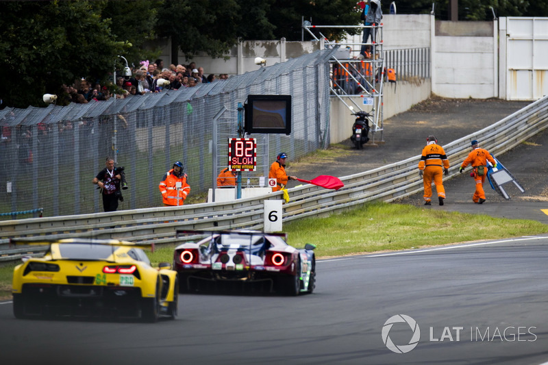 Marshals recover debris from the track during a red flag