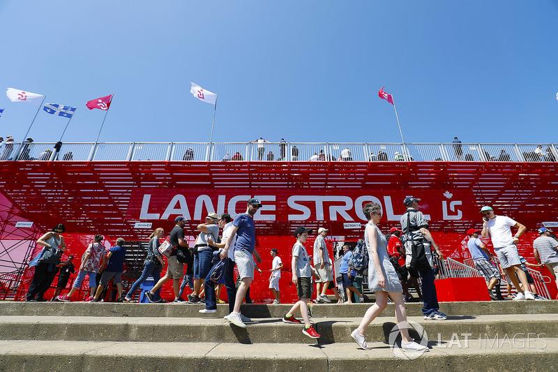 Des fans marchent devant la tribune Lance Stroll