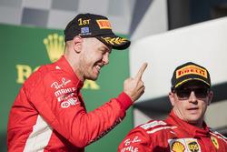 Sebastian Vettel, Ferrari, 1st position, celebrates on the podium alongside Kimi Raikkonen, Ferrari, 3rd position