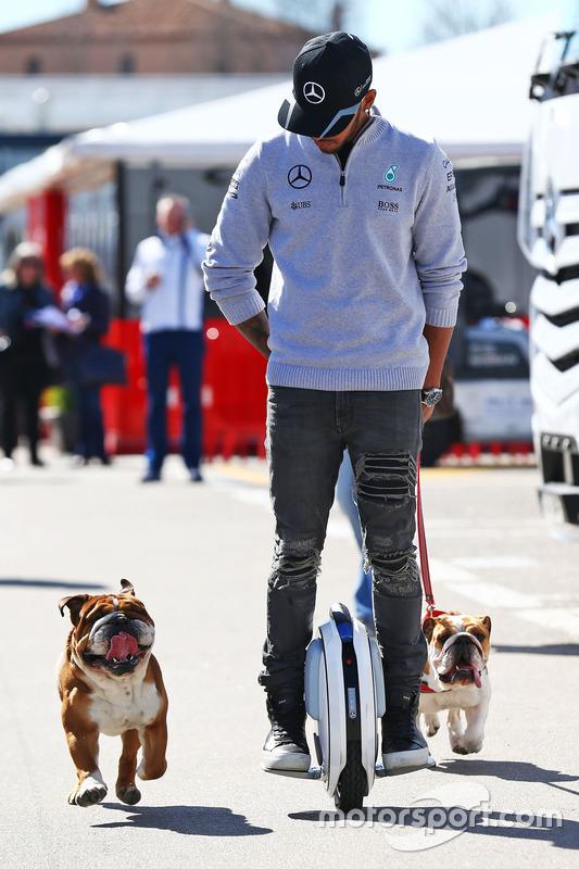 Lewis Hamilton, de Mercedes AMG F1 en un hoverboard en el paddock con su perros Roscoe y Coco