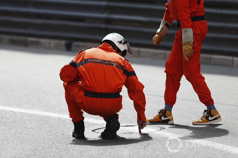 A marshal inspects a drain cover during a red flag period in FP2