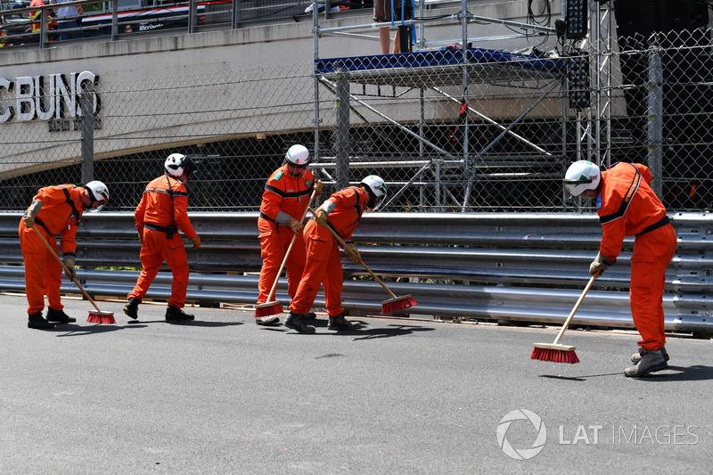 Les commissaires nettoient la piste après le crash de Max Verstappen, Red Bull Racing RB14