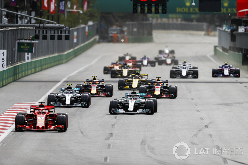 Sebastian Vettel, Ferrari SF71H, leads Lewis Hamilton, Mercedes AMG F1 W09, Valtteri Bottas, Mercedes AMG F1 W09, Daniel Ricciardo, Red Bull Racing RB14 Tag Heuer, Max Verstappen, Red Bull Racing RB14 Tag Heuer, and the rest of the field after a restart