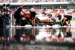 Engineers return Romain Grosjean, Haas F1 Team VF-18, to the garage