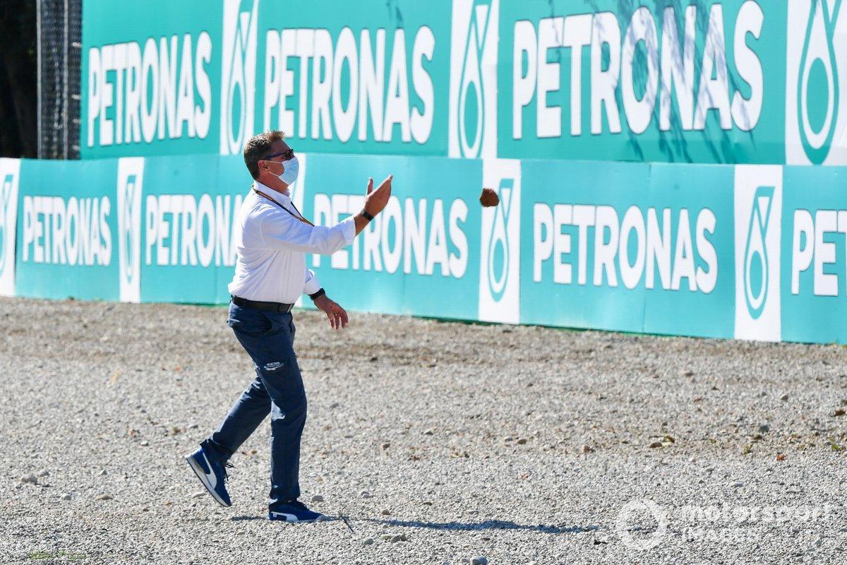 Un representante de la FIA con una piedra de la zona de grava