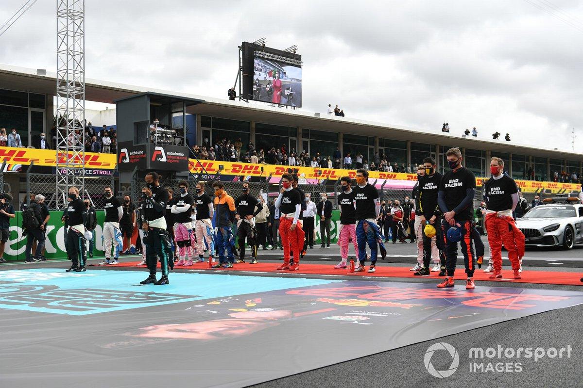 """Los pilotos se ponen de pie para el himno nacional antes de la salida en sus camisetas de """"End Racism""""."""