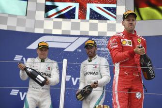 Sebastian Vettel, Ferrari, Lewis Hamilton, Mercedes AMG F1 and Valtteri Bottas, Mercedes AMG F1 celebrate with the champagne on the podium
