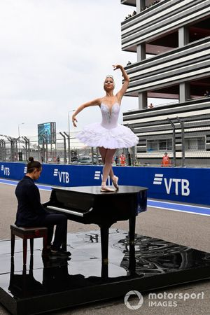 A balerina performs on top of a piano prior to the start