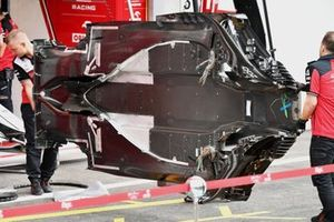Alfa Romeo Racing mechanics carry the floor of one Alfa Romeo Racing C41