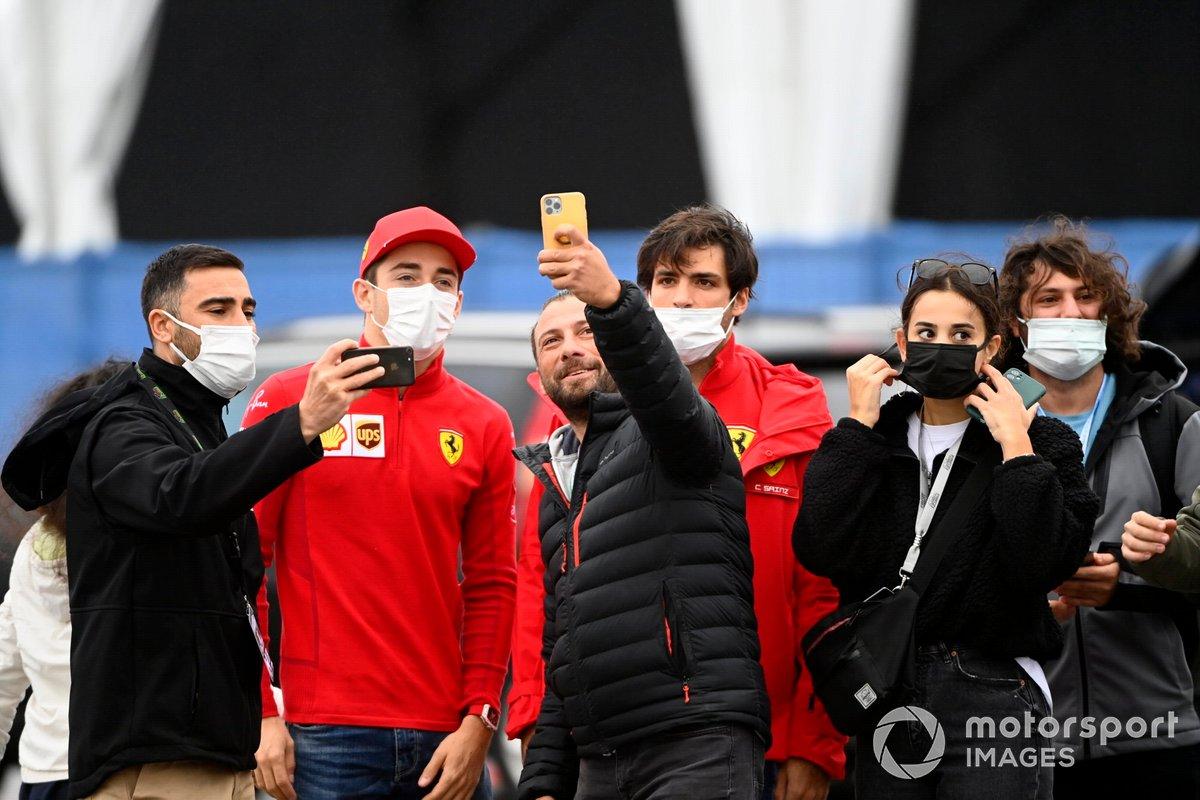 Charles Leclerc, de Ferrari, y Carlos Sainz Jr., de Ferrari, posan con los aficionados para un selfie a su llegada al circuito