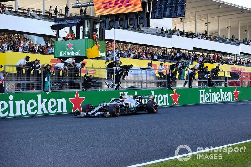 Valtteri Bottas, Mercedes AMG W10, 1st position, takes the chequered flag and passes his team on the pit wall