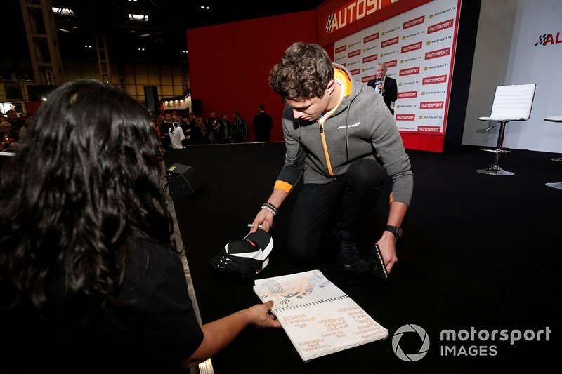 Lando Norris, McLaren signs caps and a fan's notebook