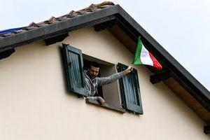 Een fan met een Italiaanse vlag vanuit een raam