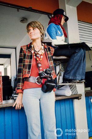 Une photographe dans la voie des stands à côté d'une femme qui note les temps