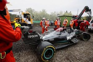 Marshals clear the damaged car of Valtteri Bottas, Mercedes W12, from the gravel trap