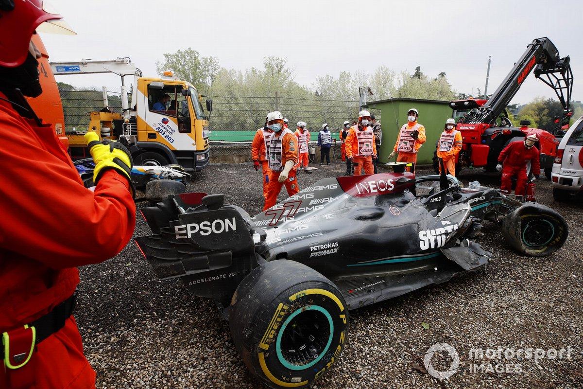 Los oficiales de pista despejan el coche dañado de Valtteri Bottas, Mercedes W12, de la trampa de grava