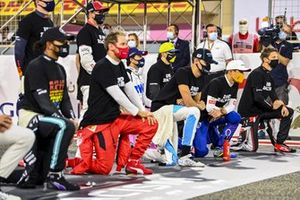 The drivers stand and kneel in support of the End Racsim campaign prior to the start