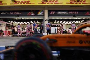 Un McLaren pasa por el garaje de boxes de Racing Point de Lance Stroll, Racing Point RP20 y Sergio Pérez, Racing Point RP20