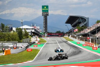 Romain Grosjean, Haas F1 Team VF-19, leads George Russell, Williams Racing FW42