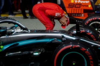 Sebastian Vettel, Ferrari, inspects the car of his rival Lewis Hamilton, Mercedes AMG F1 W10, in Parc Ferme