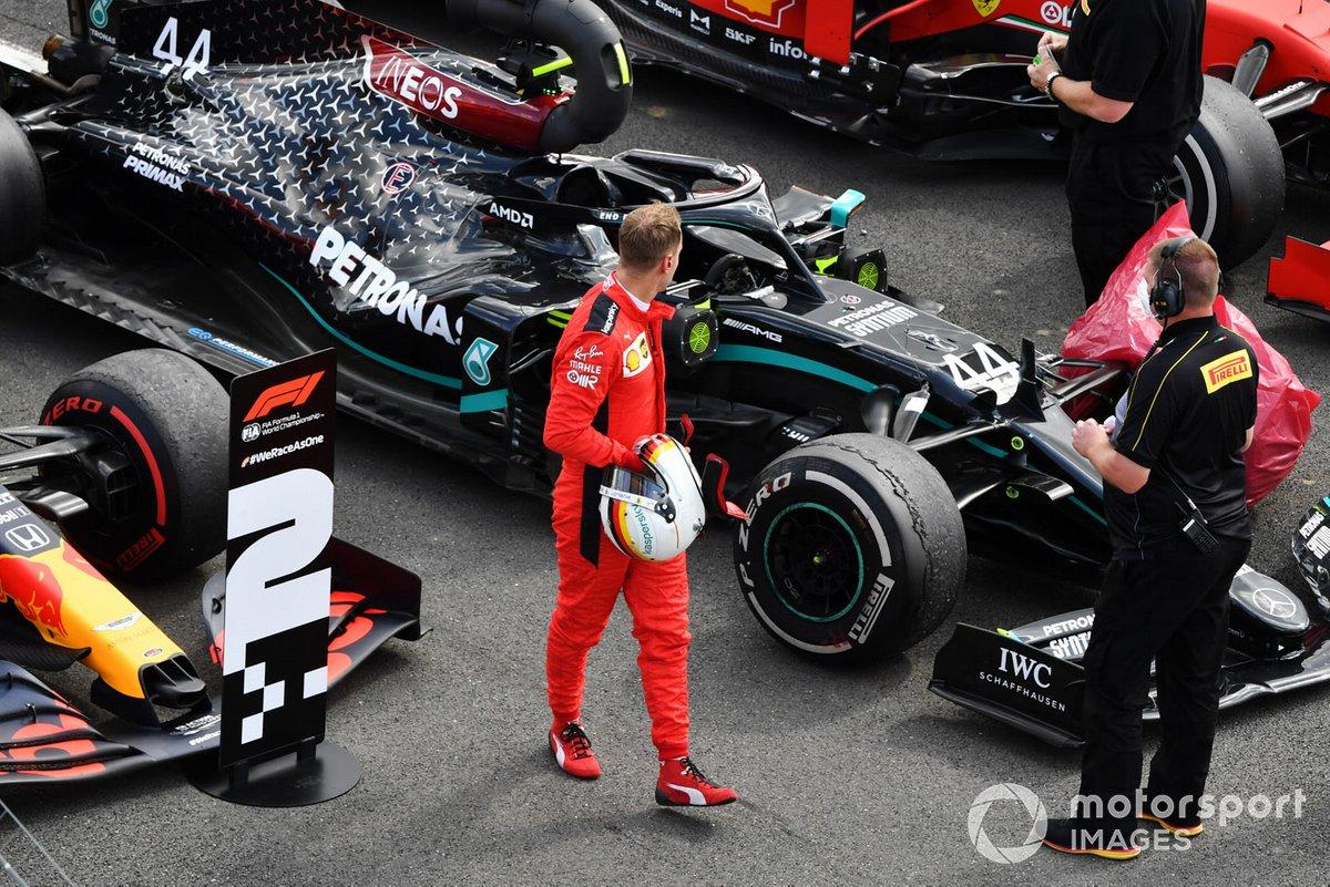 Sebastian Vettel, Ferrari, observa el neumático pinchado del monoplaza de Lewis Hamilton, Mercedes F1 W11, en Parc Ferme