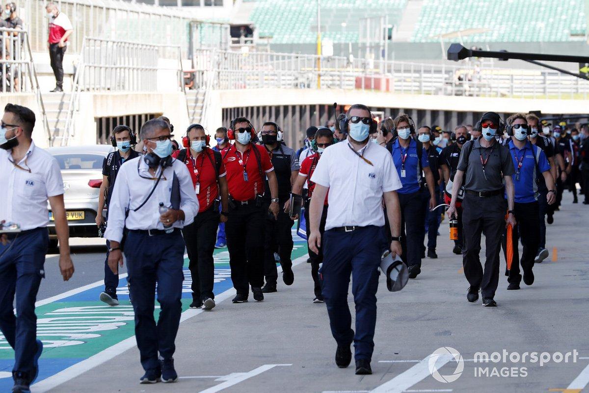 Los delegados de la FIA y los miembros del equipo en el pit lane
