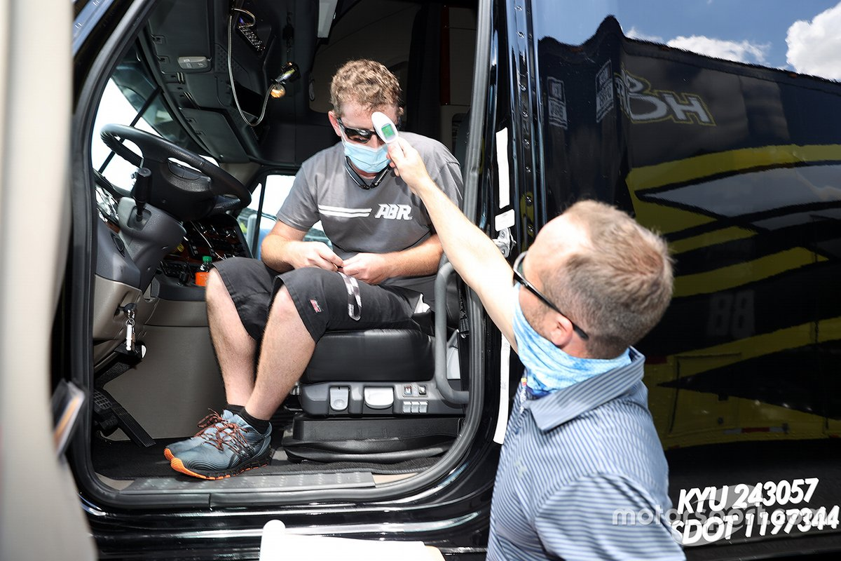 A driver for a team hauler has their temperature checked