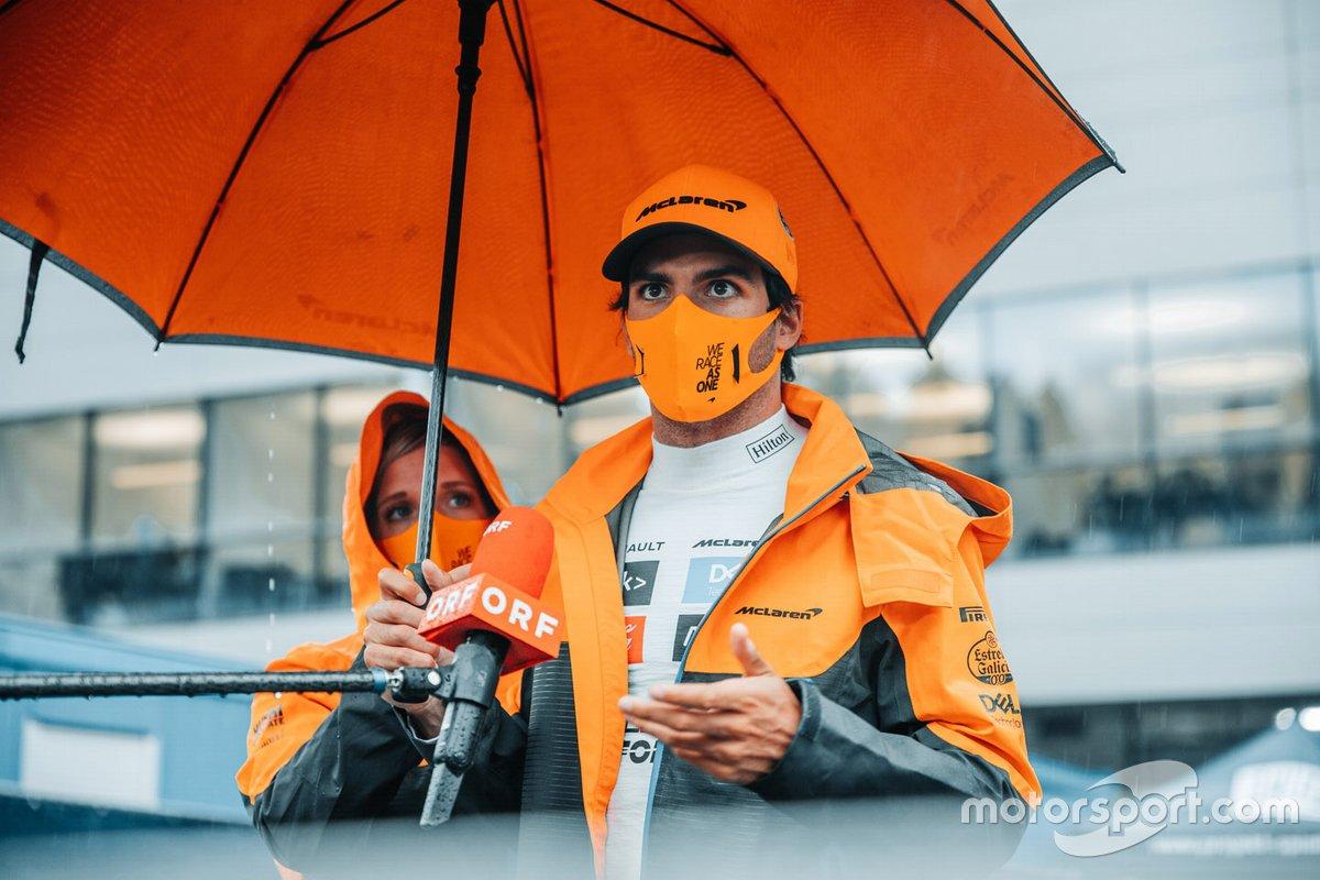 Carlos Sainz Jr, McLaren, se refugia bajo un paraguas