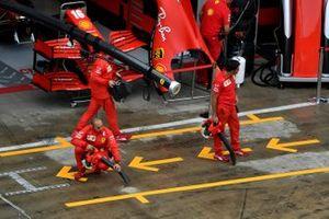 Механики Ferrari высушивают асфальт перед своими боксами