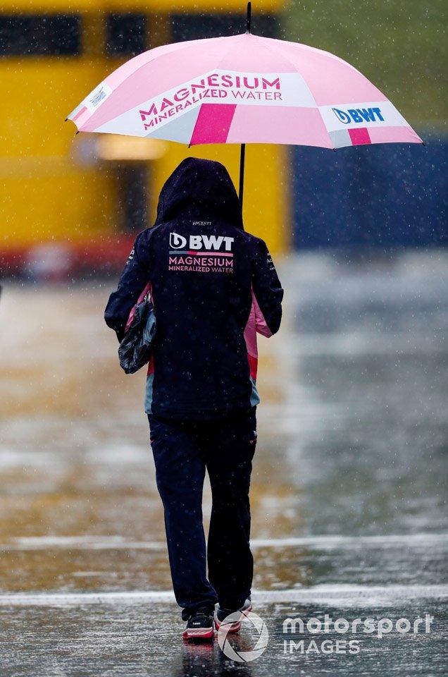 Un miembro de Racing Point llega al circuito con paraguas