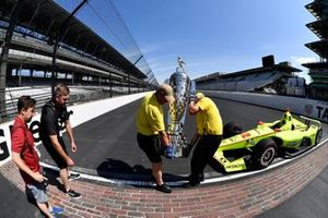 Yellow shirts move the Borg-Warner trophy into place
